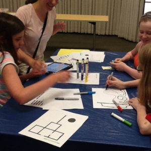 Girls sit at a table creating circuits for textiles.