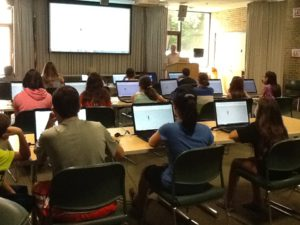 A room of young people sit facing a large screen with their laptops open in front of them.
