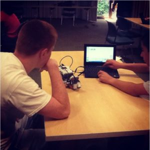 Two boys programming a home made robot with a laptop.
